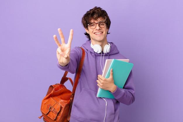 Młody student uśmiechający się i wyglądający przyjaźnie, pokazujący numer trzy
