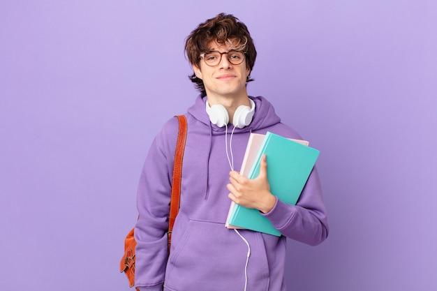 Młody student uśmiechający się radośnie z ręką na biodrze i pewny siebie