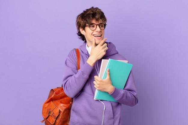 Młody student uśmiechający się ze szczęśliwym, pewnym siebie wyrazem twarzy z ręką na brodzie