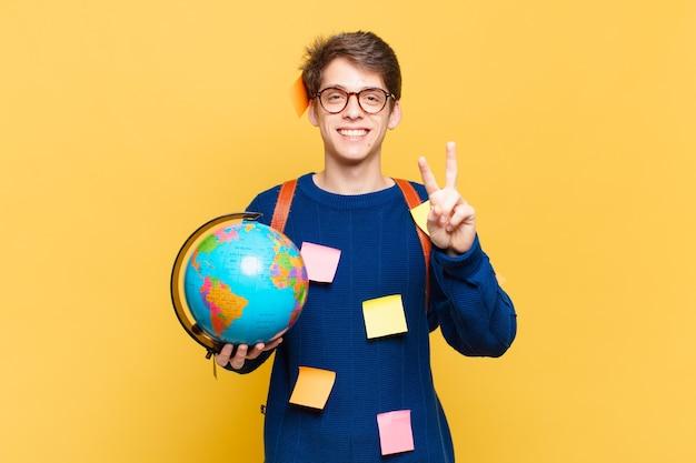 Młody student, uśmiechnięty i wyglądający na szczęśliwego, beztroskiego i pozytywnego, gestykulujący zwycięstwo lub pokój jedną ręką