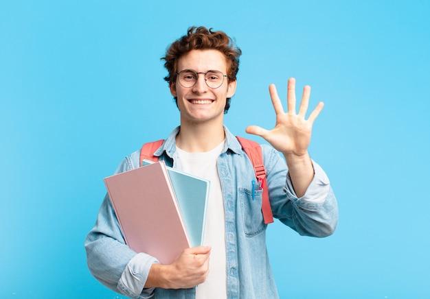 Młody student, uśmiechnięty i wyglądający przyjaźnie, pokazujący cyfrę piątą lub piątą z ręką do przodu, odliczający w dół