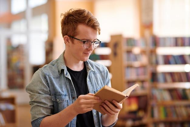 Młody student w dżinsowej koszuli i czarnej koszulce, czytając książkę w bibliotece przed seminarium