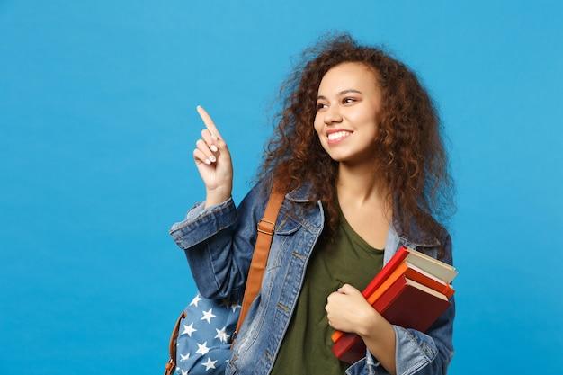 Młody student w dżinsowych ubraniach i plecaku trzyma książki izolowane na niebieskiej ścianie