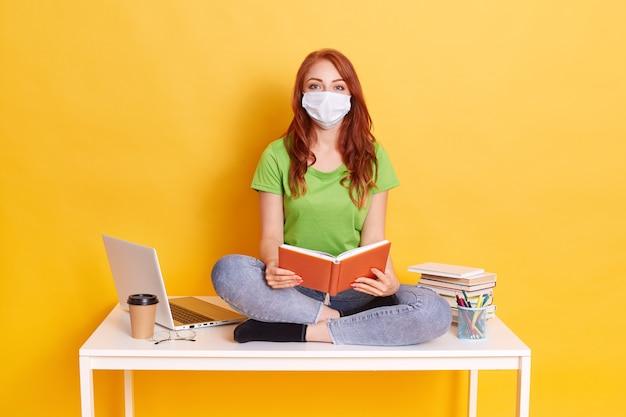 Młody student w masce medycznej studiuje w domu podczas kwarantanny, znudzony kształceniem na odległość, siedzi ze skrzyżowanymi nogami na białym stole z książką w rękach.