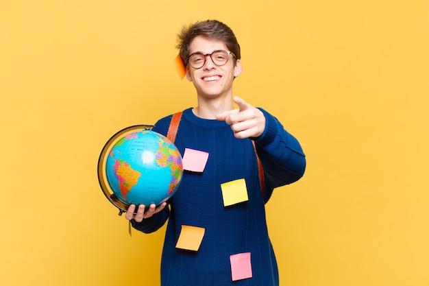 Młody student wskazujący na aparat z zadowolonym, pewnym siebie, przyjaznym uśmiechem, wybierający ciebie