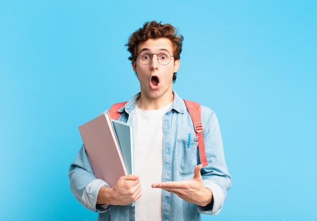 Młody student wyglądający na zaskoczonego i zszokowanego, z opuszczoną szczęką, trzymający przedmiot z otwartą dłonią z boku