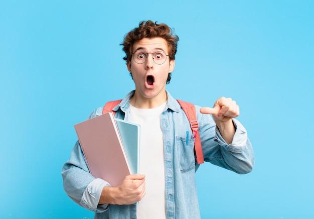 """Młody student wyglądający na zdziwionego z niedowierzaniem, wskazujący na przedmiot z boku i mówiący """"wow, niewiarygodne"""""""