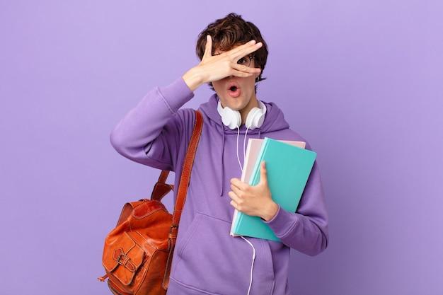 Młody student wyglądający na zszokowanego, przestraszonego lub przerażonego, zakrywający twarz dłonią