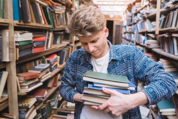 Młody student z dużą ilością książek w rękach biblioteki.