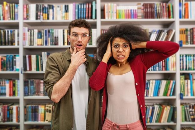 Młody student z zmartwionym wyrazem twarzy w bibliotece