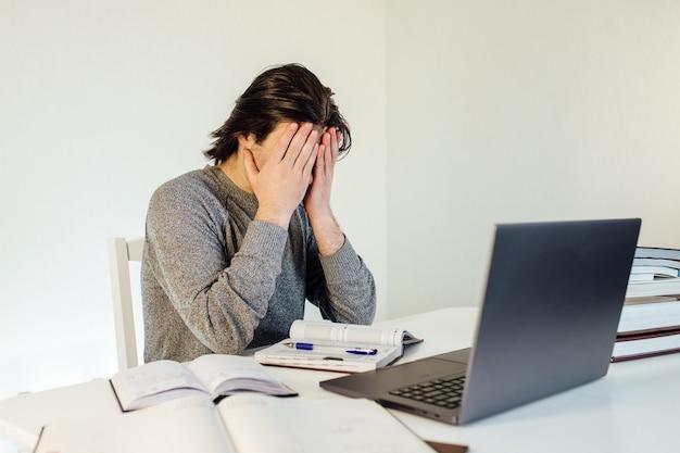Młody student za pomocą laptopa pracującego w domu w internecie. zmęczony facet, pociera twarz. nauka w domu, nauka na odległość i praca jako freelancer