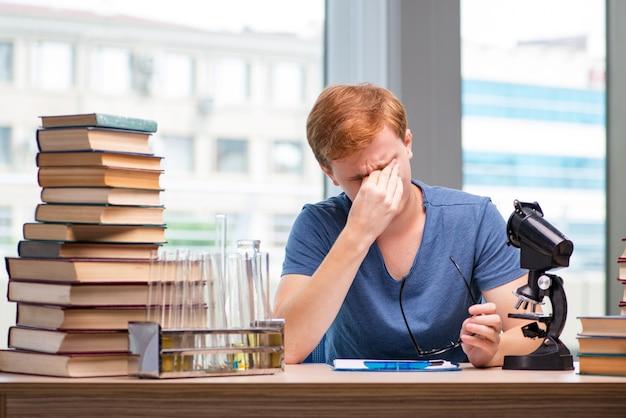 Młody student zmęczony i wyczerpany przygotowuje się do egzaminu chemicznego