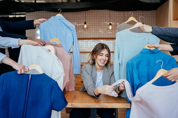 Młody stylista przeglądający zestaw koszulek do fotografowania mody