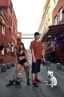 Młody, stylowo ubrany mężczyzna i kobieta o atletycznej sylwetce z dwoma amerykańskimi bully dogami na ulicach miasta.