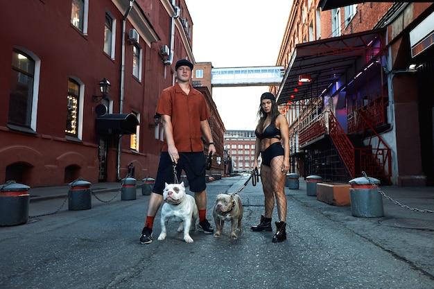 Młody, stylowo ubrany mężczyzna i kobieta o atletycznej sylwetce z dwoma amerykańskimi psami bully na ulicach miasta.