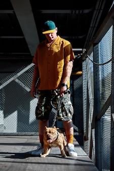 Młody stylowo ubrany mężczyzna z amerykańskim psem bully na ulicach miasta