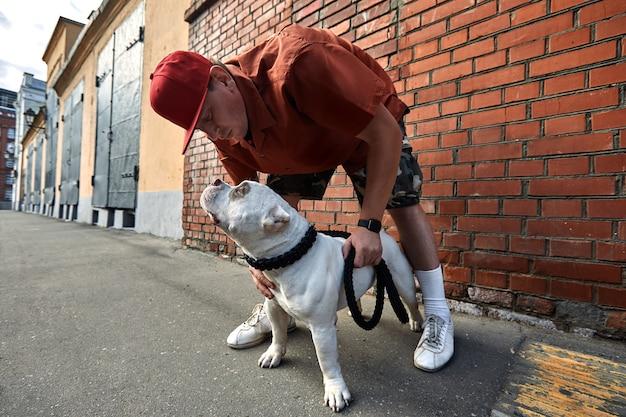 Młody stylowo ubrany mężczyzna z dwoma amerykańskimi psami bully na ulicach miasta.