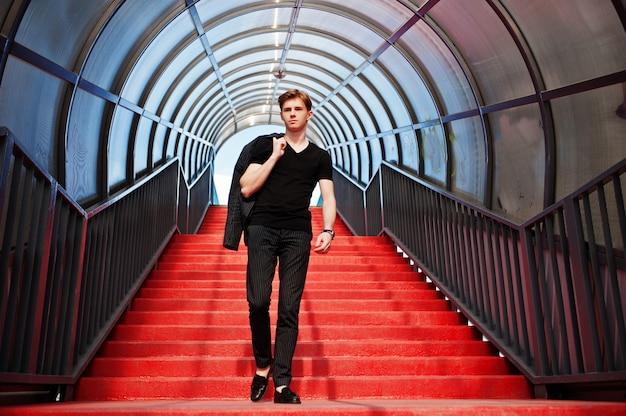 Młody stylowy chłopak macho w czarnej kurtce pozował na zewnątrz ulicy. zadziwiający wzorcowy mężczyzna przy czerwonym schodka tonnelem.