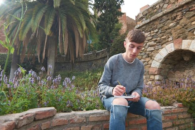 Młody, stylowy facet rasy kaukaskiej siedzący w ogrodzie, odrabiający pracę domową