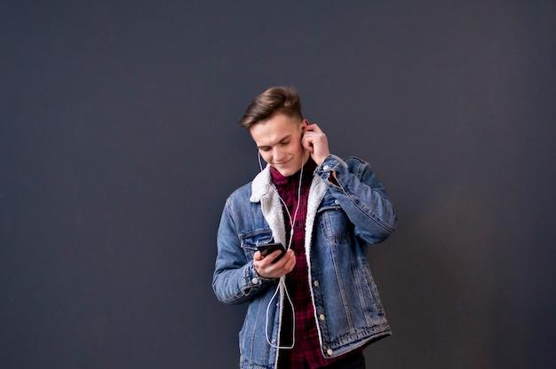 Młody stylowy facet w dżinsowej kurtce słucha muzyki na słuchawkach