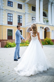 Młody stylowy facet w garniturze pana młodego i panny młodej piękna dziewczyna w białej sukni z pociągiem spacer po parku w dniu ślubu