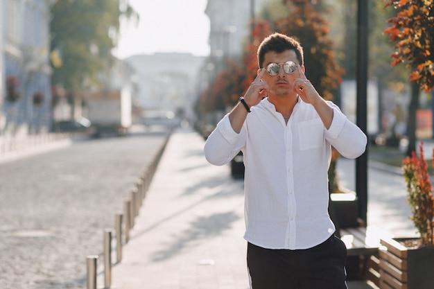 Młody stylowy facet w koszuli idąc europejską ulicą w słoneczny dzień