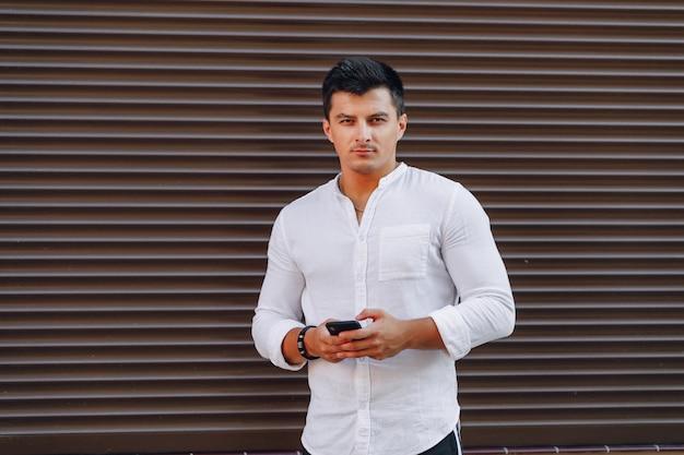 Młody stylowy facet w koszuli pisania na telefon