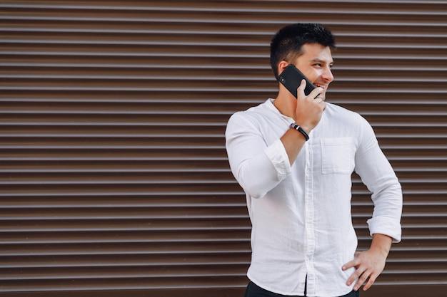 Młody stylowy facet w koszuli rozmawia przez telefon na proste