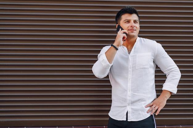 Młody stylowy facet w koszuli rozmawia przez telefon na prostej powierzchni