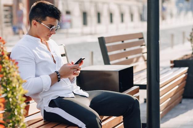 Młody stylowy facet w koszuli z telefonem na ławce w słoneczny ciepły dzień na zewnątrz