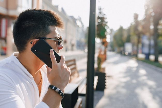 Młody stylowy facet w koszuli z telefonem na ławce w słoneczny dzień na zewnątrz