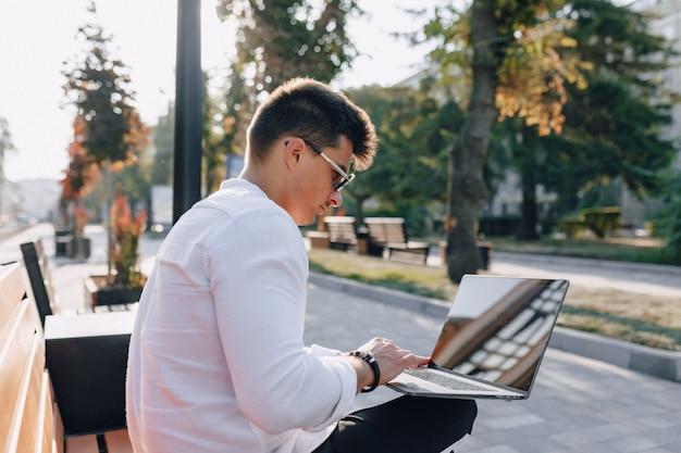 Młody stylowy facet w koszuli z telefonu i notebooka na ławce w słoneczny ciepły dzień na zewnątrz, niezależny