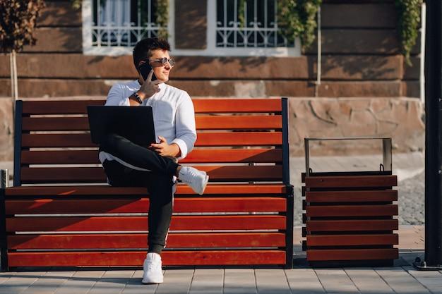 Młody stylowy facet w koszuli z telefonu i notebooka na ławce w słoneczny dzień na zewnątrz