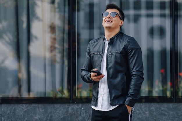 Młody stylowy facet w okularach w czarnej skórzanej kurtce z telefonem na powierzchni szkła