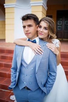 Młody stylowy facet w stroju pana młodego i panny młodej piękna dziewczyna w białej sukni z pociągiem chodzącym na tle dużego domu z kolumnami w dniu ślubu