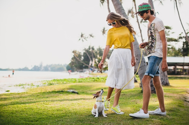 Młody stylowy hipster para zakochanych, spacery i zabawy z psem na tropikalnej plaży