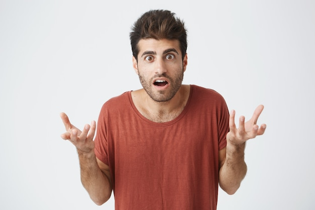 Młody stylowy hiszpański facet w czerwonej koszulce z szeroko otwartymi ustami, trzymając ręce w zaskoczonym geście zszokowany swoją ulubioną drużyną piłkarską przegraną w meczu. język ciała