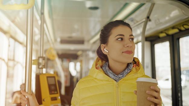 Młody stylowy kobieta pasażer korzystający z podróży środkami transportu publicznego, stojący z kawą w nowoczesnym tramwaju