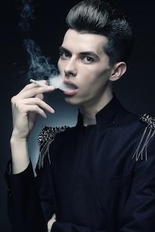 Młody stylowy mężczyzna pali papierosa