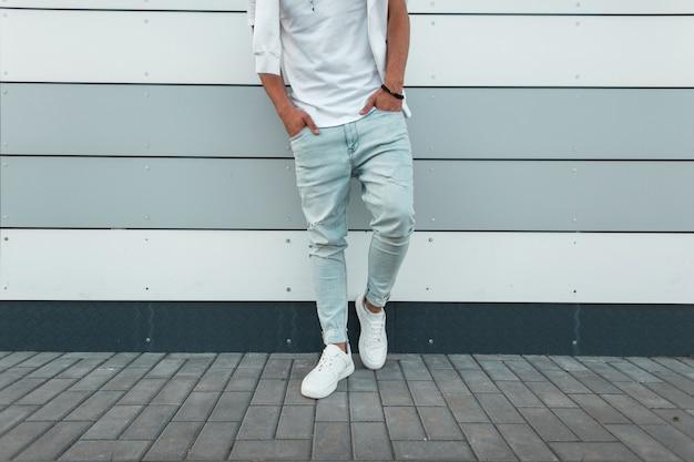 Młody stylowy mężczyzna w białej modnej koszulce w vintage niebieskie dżinsy w białych modnych trampkach stoi w pobliżu nowoczesnej ściany.