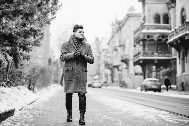 Młody stylowy mężczyzna w ciepłym szarym płaszczu i skórzanych rękawiczkach idąc ulicą. styl uliczny. styl uliczny. obraz czarno-biały.