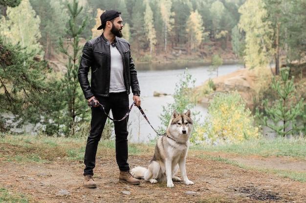 Młody stylowy mężczyzna w czarnej skórzanej kurtce i dżinsach, stojąc na chodniku w lesie lub parku, trzymając smycz swojego zwierzaka