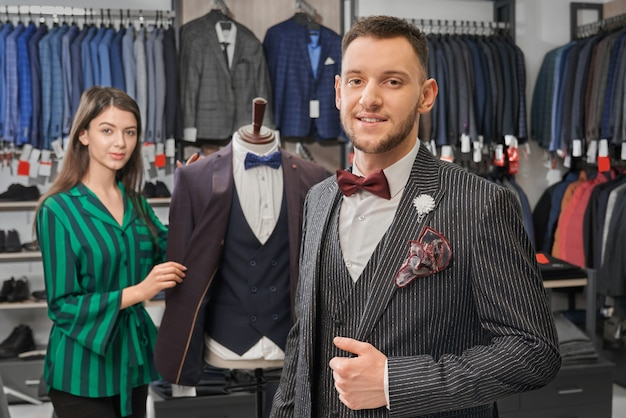Młody, stylowy mężczyzna w eleganckim garniturze pozowanie w sklepie.