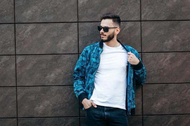 Młody stylowy mężczyzna z brodą w białej koszulce i okularach przeciwsłonecznych