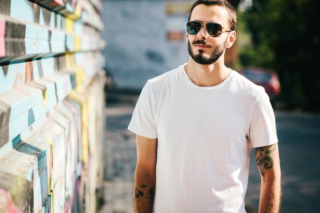 Młody stylowy mężczyzna z brodą w białej koszulce i okularach