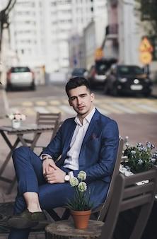 Młody stylowy pewnie przystojny biznesmen model w garnitur tkaniny na ulicy. wygląd mody