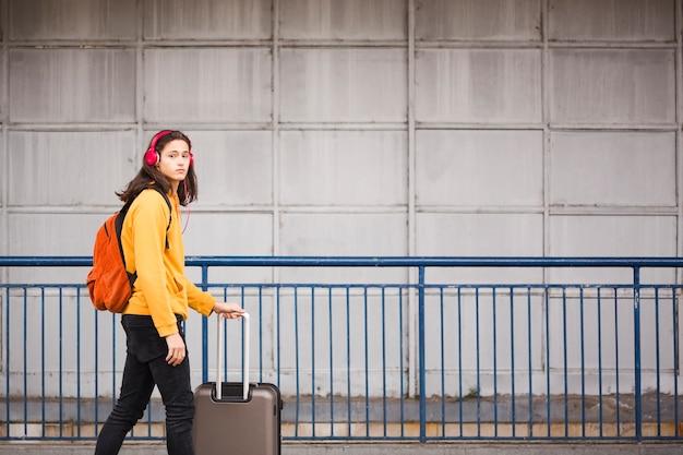 Młody stylowy podróżnik z bagażem