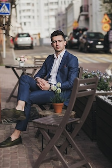 Młody stylowy przystojny biznesmen model w garniturze, siedząc na ulicy. wygląd mody