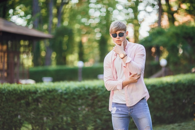 Młody, stylowy, przystojny facet w zwykłych ubraniach, okularach przeciwsłonecznych i zegarze stoi na kampusie