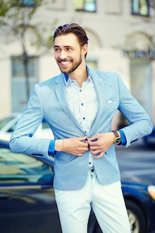 Młody stylowy przystojny mężczyzna w garniturze na ulicy